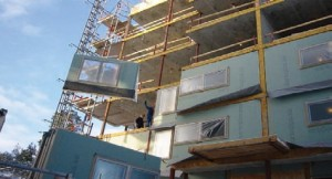 Assembling_pre_fabricated_wood_frame_exterior_infill_wall_panels_in_a_multi_storey_concrete_structure_building_Europe[125]